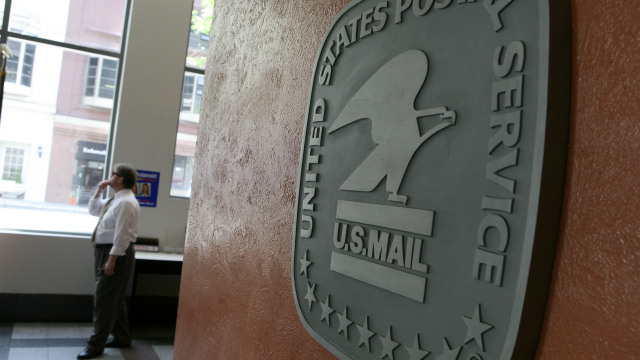 SAN FRANCISCO - MAY 11:  A man walks by a sign in the lobby of a post office May 11, 2009 in San Francisco, California.  The price of a first class postage stamp is increasing two cents to 44 cents today as the US Postal Service struggles with rising operational costs.  (Photo by Justin Sullivan/Getty Images)