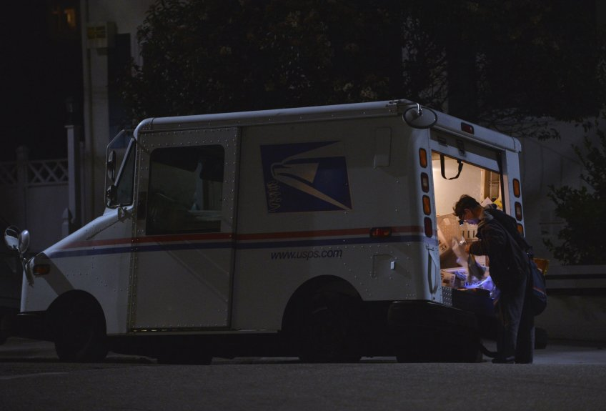 A postal worker makes his rounds in Oakland, Calif., on Monday, Dec. 19, 2016. (Kristopher Skinner/Bay Area News Group)