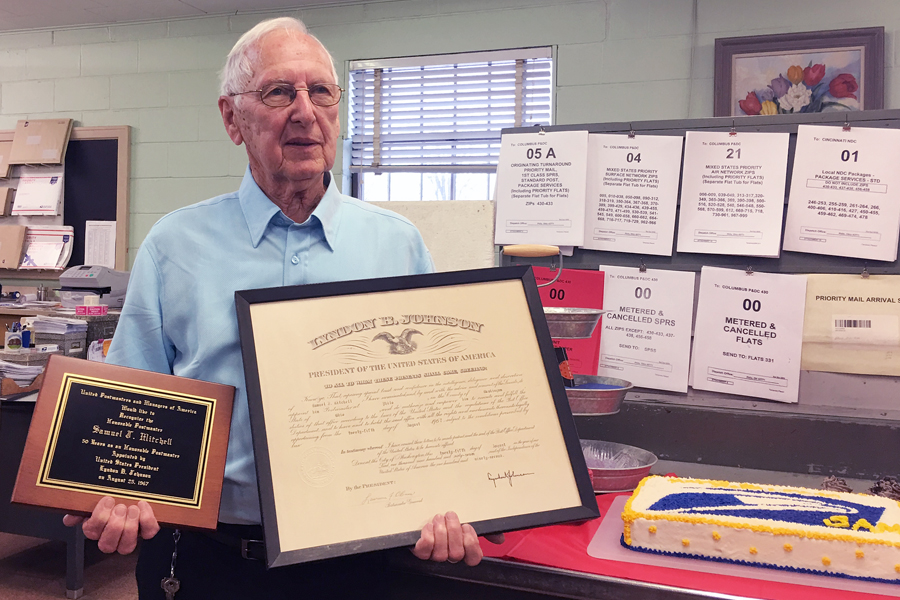 At his Jan. 31 retirement party, Samuel J. Mitchell displays a plaque and certificate he received when President Lyndon Johnson appointed him Postmaster of Philo, OH.